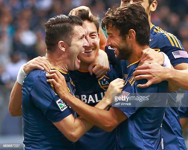 Stefan Ishizaki of the Los Angeles Galaxy is congratulated by teammates Robbie Keane and Landon Donovan as he celebrates his goal against the...