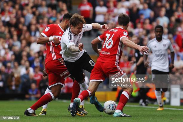 Stefan Johansen of Fulham holds off the challenge of Cyrus Christie and Jonny Howson of Middlesbrough during the Sky Bet Championship match between...