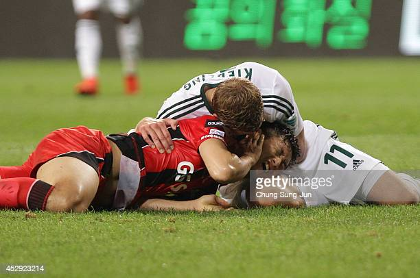 Stefan Kiessing of Bayer Leverkusen and Lee WoongHee react during the match between Bayer Leverkusen and FC Seoul as a part of Bayer Leverkusen's...