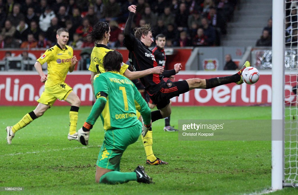 Stefan Kiessling of Leverkusen (R) scores his first goal against Roman Weidenfeller of Dortmund (2nd R) and Neven Subotic (2nd L) during the Bundesliga match between Bayer Leverkusen and Borussia Dortmund at BayArena on January 14, 2011 in Leverkusen, Germany.