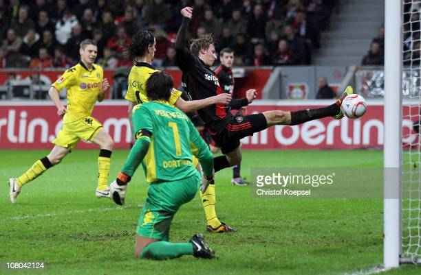 Stefan Kiessling of Leverkusen scores his first goal against Roman Weidenfeller of Dortmund and Neven Subotic during the Bundesliga match between...