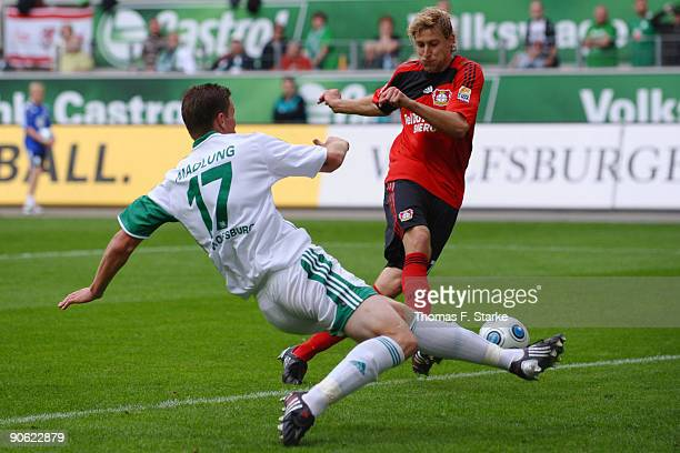 Stefan Kiessling of Leverkusen scores his team's third goal against Alexander Madlung during the Bundesliga match between VfL Wolfsburg and Bayer...