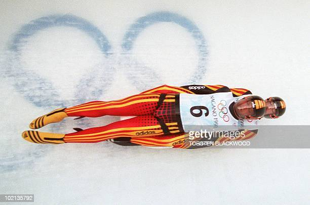 Stefan Krausse and Jan Behrendt of Germany pass the Olympic rings on the Spiral ice track during the men's Olympic double luge competition in Nagano...