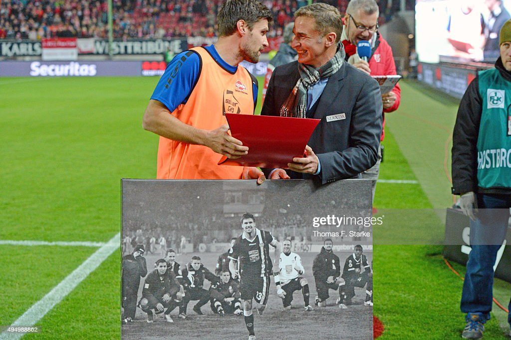 Stefan Kuntz (R), CEO of Kaiserslautern, hands out a gift to former Kaiserslautern player Florian Dick of Bielefeld prior to the Second Bundesliga match between 1. FC Kaiserslautern and Arminia Bielefeld at Fritz-Walter-Stadion on October 30, 2015 in Kaiserslautern, Germany.