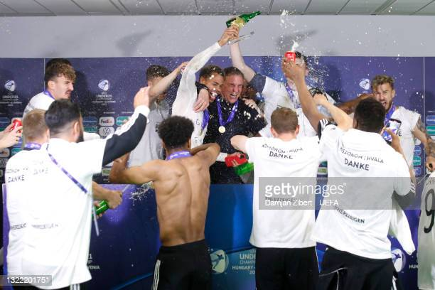 Stefan Kuntz, Head Coach of Germany celebrate with his players during a press conference after winning the 2021 UEFA European Under-21 Championship...