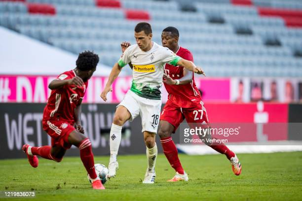 Stefan Lainer of Borussia Moenchengladbach and Alphonso Davies of FC Bayern Muenchen battle for the ball during the Bundesliga match between FC...