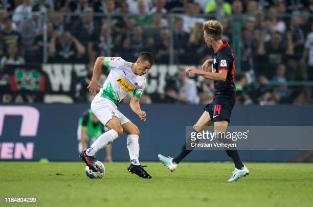 Stefan Lainer of Borussia Moenchengladbach and Kevin Kampl of RB Leipzig battle for the ball during the Bundesliga match between Borussia...