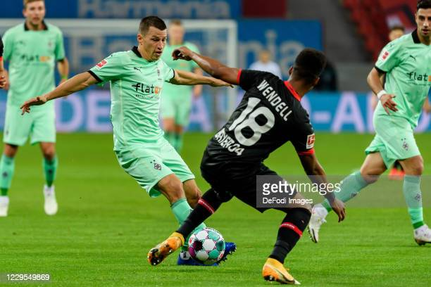 Stefan Lainer of Borussia Moenchengladbach and Wendell of Bayer 04 Leverkusen battle for the ball during the Bundesliga match between Bayer 04...
