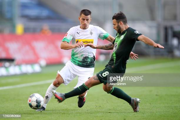 Stefan Lainer of Borussia Moenchengladbach battles for possession with Renato Steffen of VfL Wolfsburg during the Bundesliga match between Borussia...
