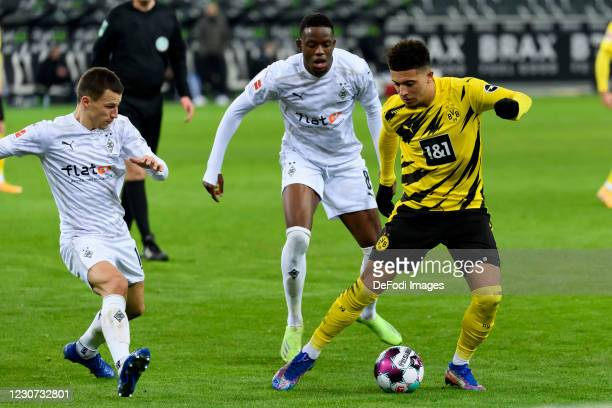 Stefan Lainer of Borussia Moenchengladbach, Denis Zakaria of Borussia Moenchengladbach and Jadon Sancho of Borussia Dortmund battle for the ball...