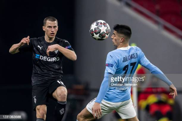 Stefan Lainer of Borussia Moenchengladbach in action with João Cancelo of Manchester City during the UEFA Champions League Round Of 16 Leg One match...