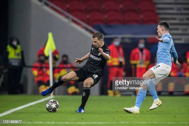 Stefan Lainer of Borussia Moenchengladbach in action with Phil Foden of Manchester City during the UEFA Champions League Round Of 16 Leg One match...
