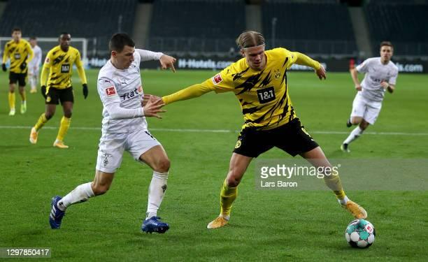 Stefan Lainer of Gladbach challenges Erling Håland of Dortmund during the Bundesliga match between Borussia Moenchengladbach and Borussia Dortmund at...