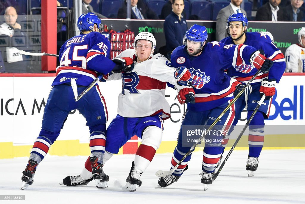 Stefan Leblanc #6 of the Laval Rocket gets caught between Brendan Guhle #45 and Colin Blackwell #43 of the Rochester Americans during the AHL game at Place Bell on October 25, 2017 in Montreal, Laval, Canada. The Rochester Americans defeated the Laval Rocket 5-2.