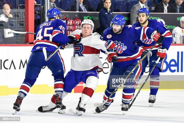 Stefan Leblanc of the Laval Rocket gets caught between Brendan Guhle and Colin Blackwell of the Rochester Americans during the AHL game at Place Bell...