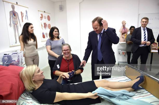 Stefan Lofven Sweden's prime minister center right checks the blood pressure of Magdalena Andersson Sweden's finance minister during a visit to the...
