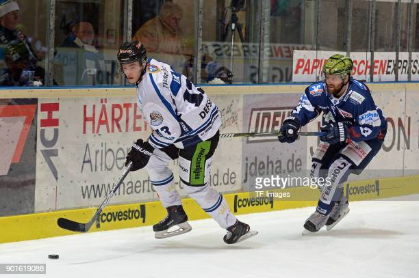 Stefan Loibl of Straubing and Johan Larsson of Iserlohn battle for the ball during the DEL match between Iserlohn Roosters and Straubing Tigers at...