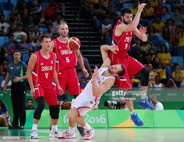 Stefan Markovic of Serbia fouls Bojan Bogdanovic of Croatia against Serbia Nemanja Nedovic of Serbia and Marko Simonovic of Serbia look on during the...