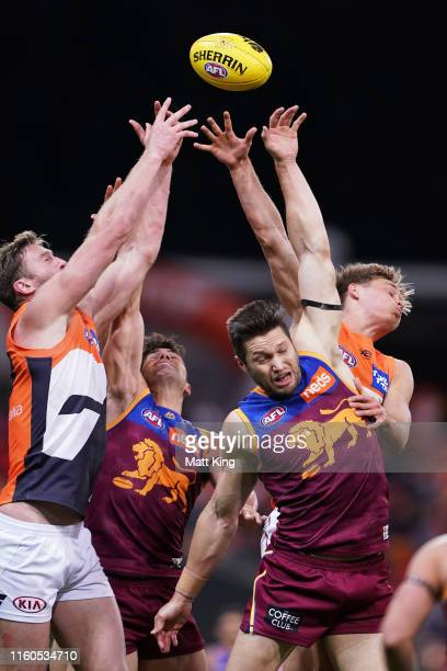 Stefan Martin of the Lions is challenged by Dawson Simpson L and Jackson Hately of the Giants during the round 16 AFL match between the Greater...