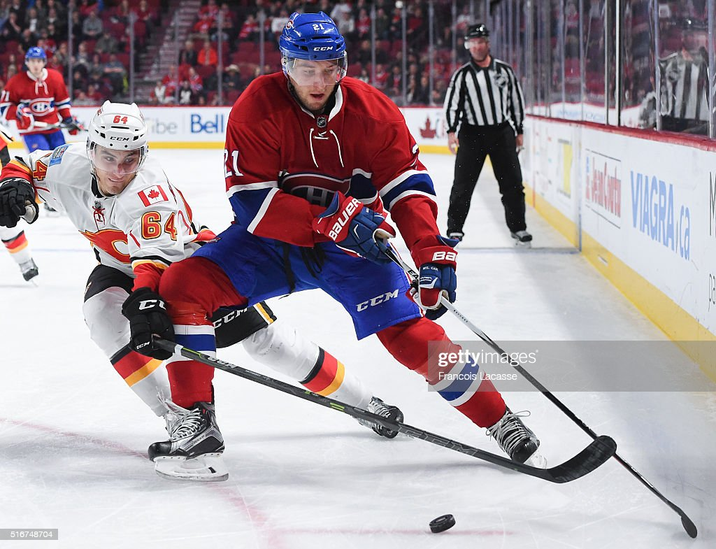 Stefan Matteau #21 of the Montreal Canadiens controls the puck against Garnet Hathaway #64 of the Calgary Flames in the NHL game at the Bell Centre on March 20, 2016 in Montreal, Quebec, Canada.