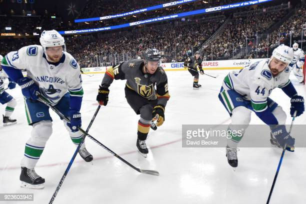 Stefan Matteau of the Vegas Golden Knights skates to the puck against Alexander Edler and Erik Gudbranson of the Vancouver Canucks during the game at...