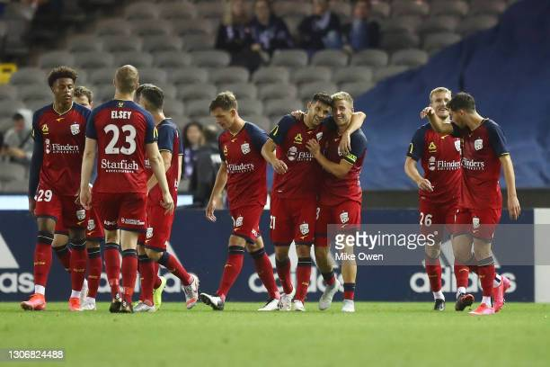 Stefan Mauk of United celebrates with teammates after scoring a goal during the A-League match between the Melbourne Victory and Adelaide United at...