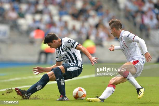 Stefan Medina of Monterrey slips on the muddy field while fighting for the ball with Isaac Brizuela of Chivas during the 9th round match between...