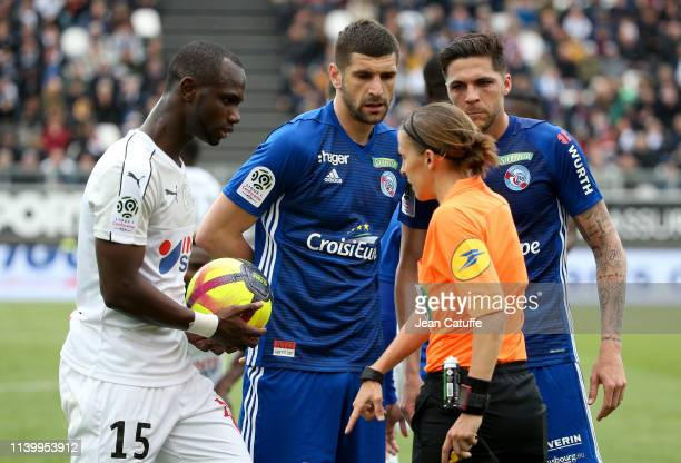 Stefan Mitrovic and Jonas Martin of Strasbourg argue with referee Stephanie Frappart first woman ro ref a Ligue 1 match while Moussa Konate of Amiens...