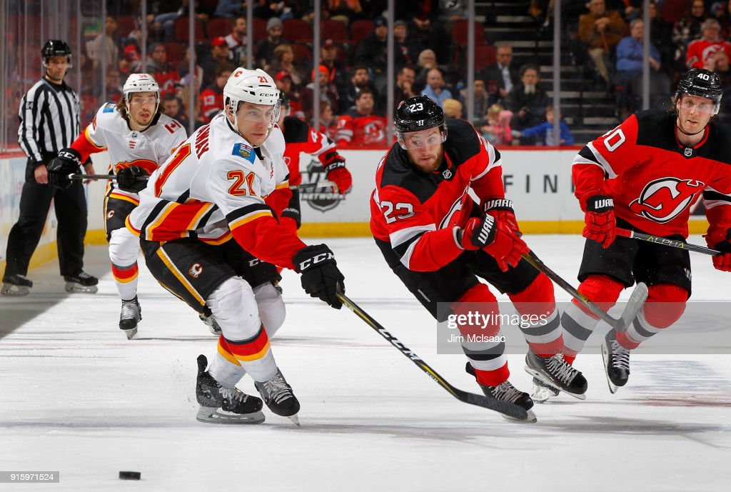 Stefan Noesen #23 of the New Jersey Devils and Garnet Hathaway #21 of the Calgary Flames chase after the puck during a game on February 8, 2018 at Prudential Center in Newark, New Jersey.