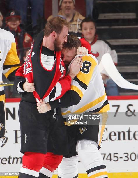Stefan Noesen of the New Jersey Devils has a fight with Ian Cole of the Pittsburgh Penguins in the first period of an NHL hockey game at Prudential...