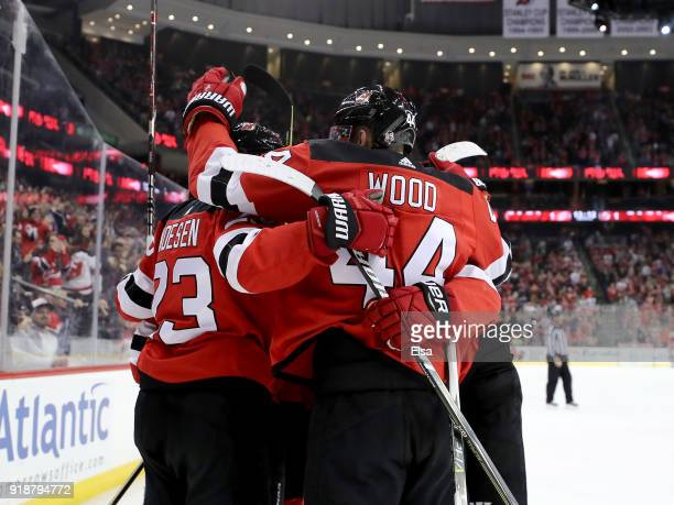 Stefan Noesen of the New Jersey Devils is congratulated by teammates Miles Wood and Travis Zajac of the New Jersey Devils after Noesen scored in the...