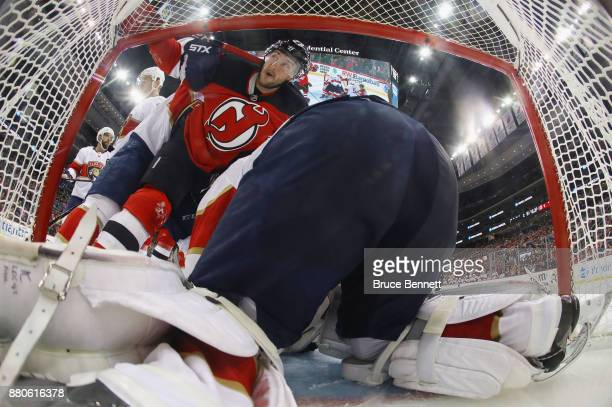 Stefan Noesen of the New Jersey Devils is pushed into the net against Roberto Luongo of the Florida Panthers at the Prudential Center on November 27...