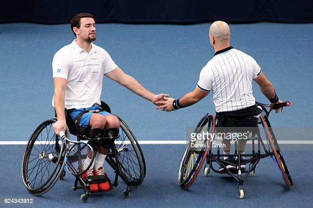 Stefan Olsson of Sweden and Joachim Gerard of Belgium tap hands between points during their men's Doubles Finals match against Gustavo Fernandez of...