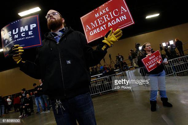Stefan Pizza a supporter of Republican presidential nominee Donald Trump holds signs before hearing him speak to supporters during a campaign event...