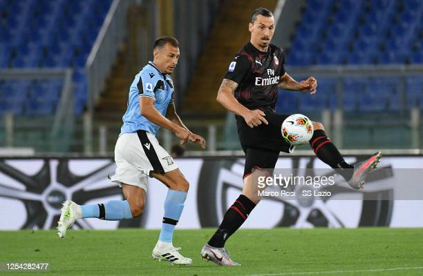 Stefan Radu of SS Lazio competes for the ball with Zlatan Ibrahimovic of AC Milan during the Serie A match between SS Lazio and AC Milan at Stadio...