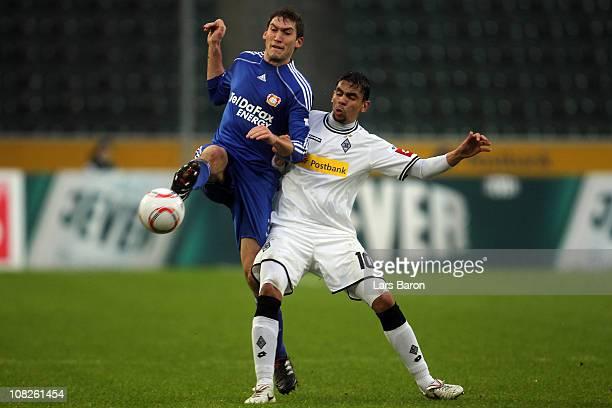 Stefan Reinartz of Leverkusen challenges Igor de Camargo of Moenchengladbach during the Bundesliga match between Borussia Moenchengladbach and Bayer...