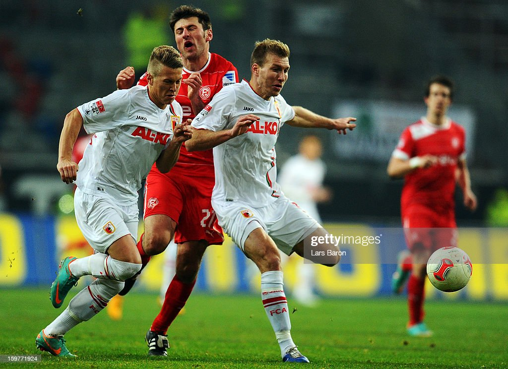 Stefan Reisinger of Duesseldorf is challenged by Ronny Philip and Ragnar Klavan of Augsburg during the Bundesliga match between Fortuna Duesseldorf 1895 and FC Augsburg at Esprit-Arena on January 20, 2013 in Duesseldorf, Germany.