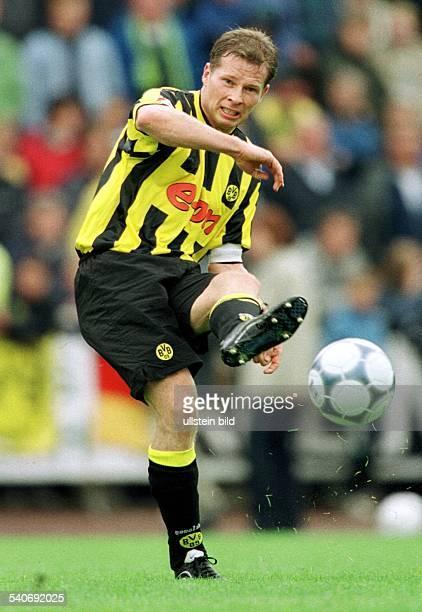 Stefan Reuter Abwehrspieler beim FußballBundesligisten Borussia Dortmund und Träger der Kapitänsbinde seiner Mannschaft hat den Ball mit seinem...