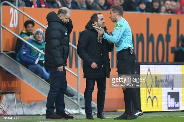 Stefan Reuter and head coach Manuel Baum of Augsburg argue with referee Tobias Stieler during the Bundesliga match between FC Augsburg and VfB...