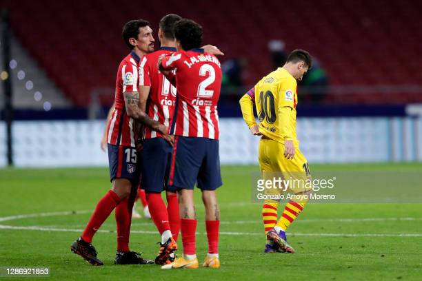 Stefan Savic, Felipe, and Jose Gimenez of Atletico de Madrid celebrate following their team's victory, as Lionel Messi of FC Barcelona looks dejected...