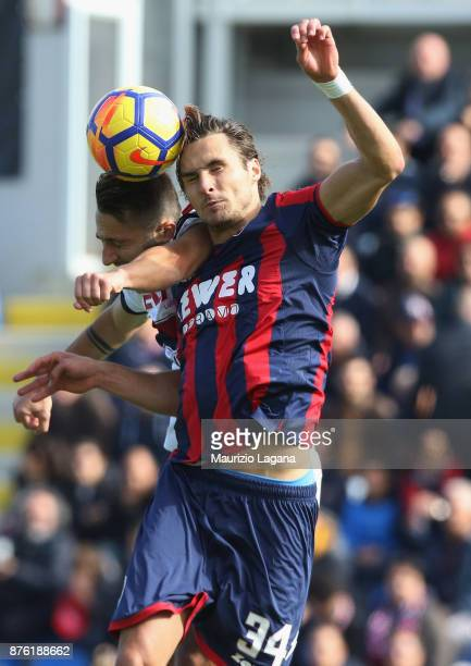 Stefan Simic of Crotone competes for the ball in air with Andrea Bertolacci of Genoa during the Serie A match between FC Crotone and Genoa CFC at...