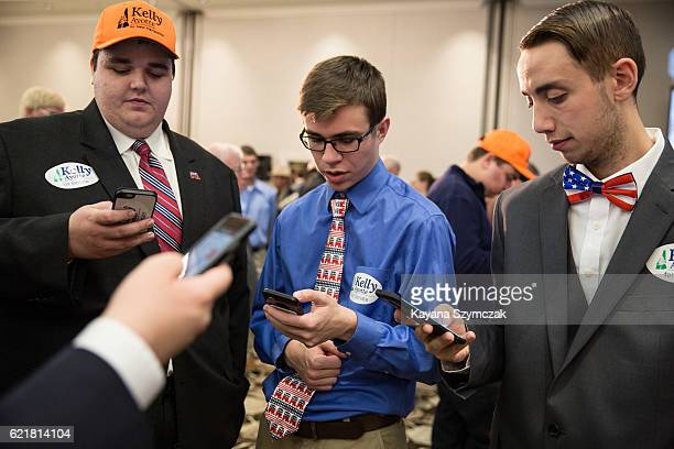 Stefan Skalinski Jack Landry and Jeremy Gaudet check election results on their phone at New Hampshire Senate candidate Kelly Ayotte's election night...