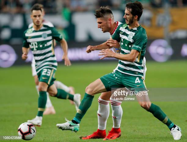Stefan Spirovski of Ferencvarosi TC competes for the ball with Tamas Takacs of DVSC in front of Lukacs Bole of Ferencvarosi TC during the Hungarian...