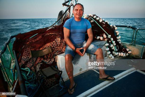 Stefan Toporau the owner of a small local fishing company poses next to one of his dolphin friendly fishing nets aboard his boat on September 1 2017...