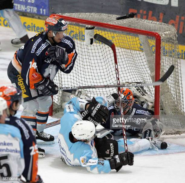 Stefan Ustorf and Daniar Dshunssow of Eisbaeren compete with Paul Manning of Freezers during the DEL match between Eisbaeren Berlin and Hamburg...