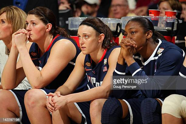 Stefanie Dolson Kelly Faris and Brianna Banks of the Connecticut Huskies look on from the bench in the second half after Dolson returned to the bench...
