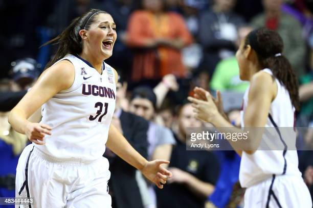 Stefanie Dolson of the Connecticut Huskies celebrates with her teammate Bria Hartley after defeating the Notre Dame Fighting Irish 79 to 58 in the...