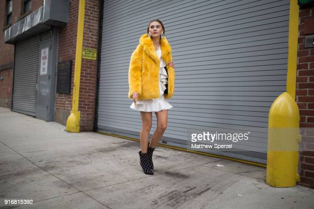 Stefanie Giesinger is seen on the street attending SelfPortrait during New York Fashion Week wearing a yellow fur coat with white dress on February...