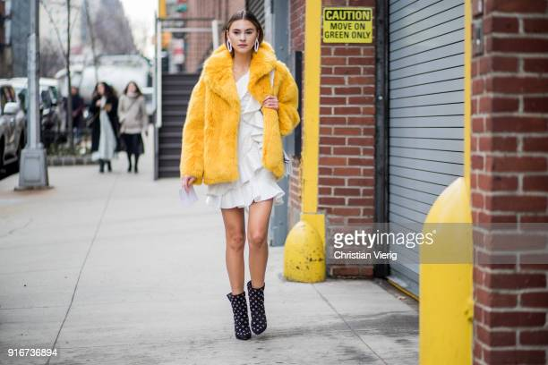 Stefanie Giesinger wearing yellow fake fur coat white dress black ankle boots seen outside SelfPortrait on February 10 2018 in New York City