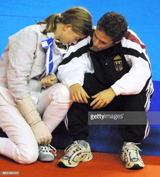 Stefanie Kubisa of the German team cries against the shoulder of trainer Martin Mundt after the defeat of her team against Russia during the...